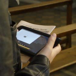 Une visiteuse dans l'église consulte une vidéo sur sa tablette
